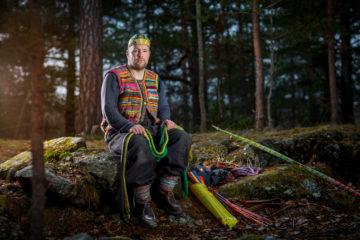 Anders Jakobsen, designer, assis sur un rocher dans la forêt suédoise tenant un arc en bois dans sa main.