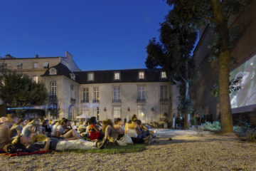 A big group of people sit in the garden of Hôtel de Marle during an outdoor cinema session.