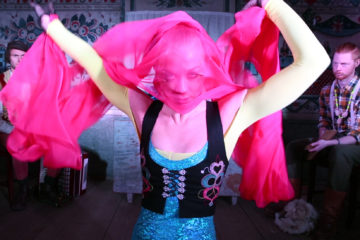 Woman dancing with pink textile in old wooden house