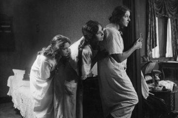 Image en noir et blanc du film Norrtullsligan : 3 femmes tapies derrières une fenêtre semblent guetter quelque chose.