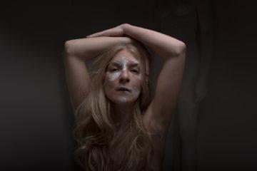 Potrati de la chanteuse Ionnalee, buste, peinture blanche sur son visage, les bras levés
