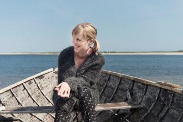potrait de la chanteuse Sofie Sörman, qui sourit de prfil, assise á l'avant d'une barque avec fond vue sur la mer