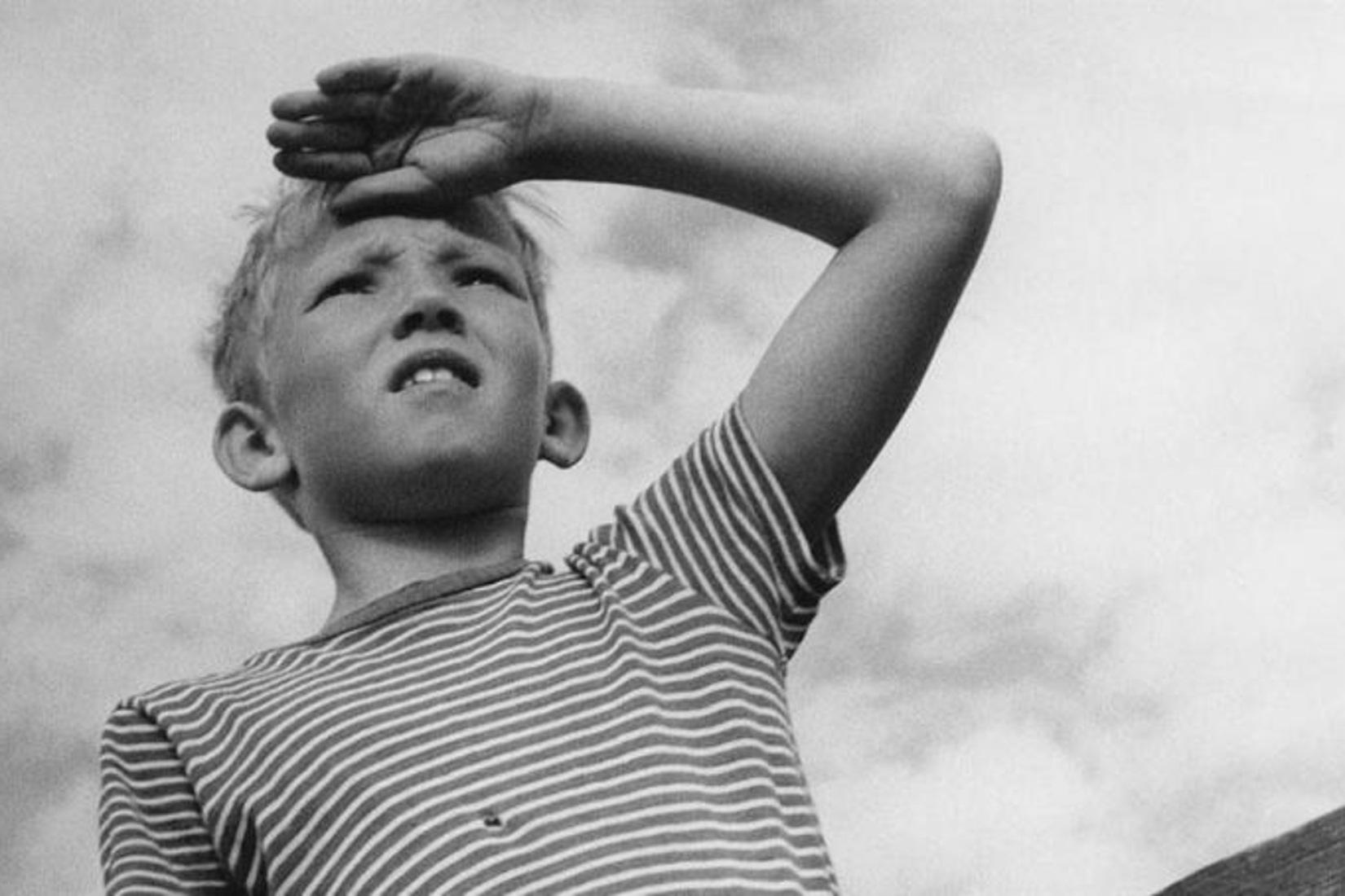 en noir et blanc, extrait de La Grande Aventure d'Arne Sucksdorff : un jeune garçon en contre plongée rregarde au loin, la main pour se protéger du soleil, sur son front