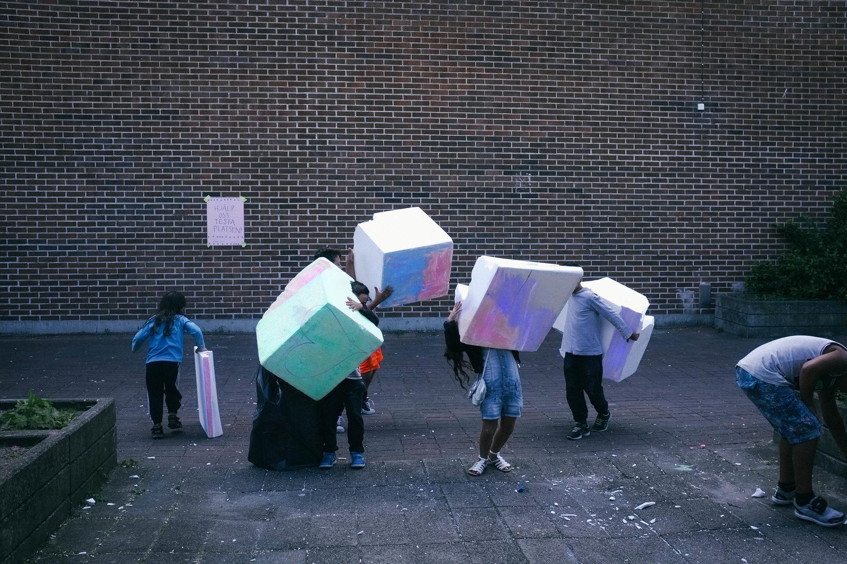 des enfants portent des cubes modulables dans la rue
