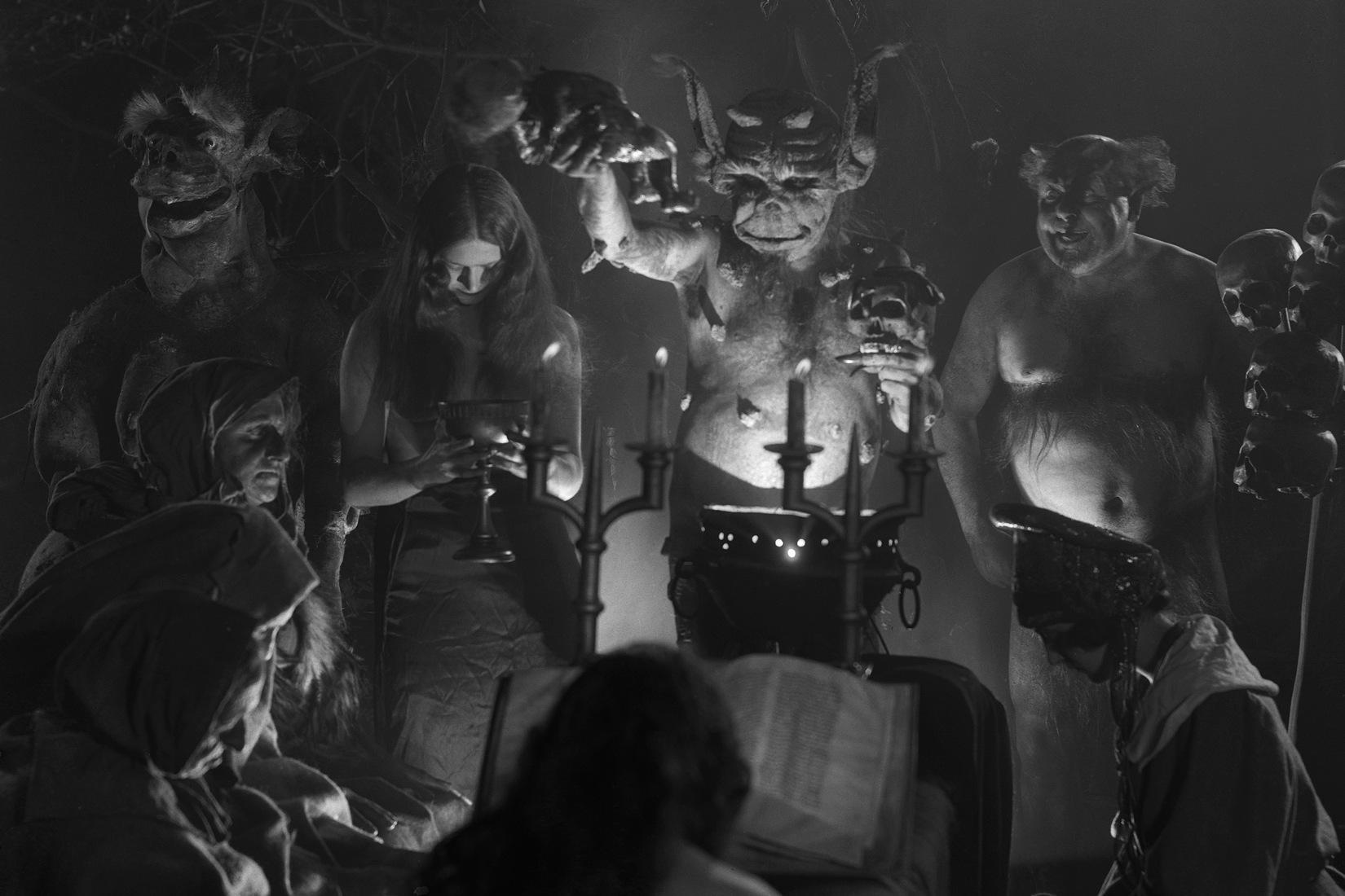 image en noir et blanc tirée du film Häxan : un rassemblement de socrières et démons éclairés par la lumière d'une bougie