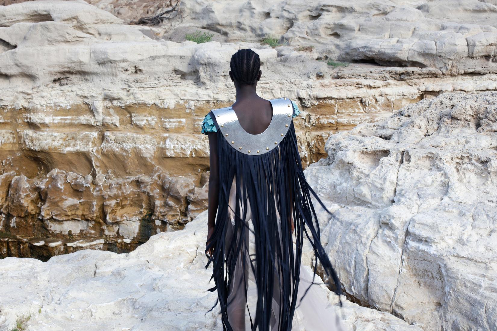 un mannequin de dos face à un paysage rocheux, porte une sorte de cape à franges un peu futuriste