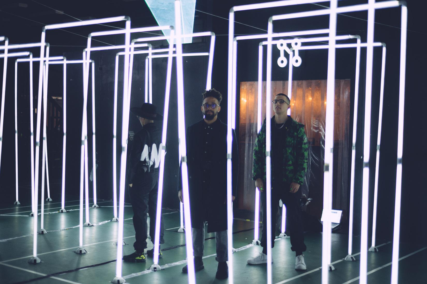 3 personnes se tiennent debout sous des structures lumineuses linéaires