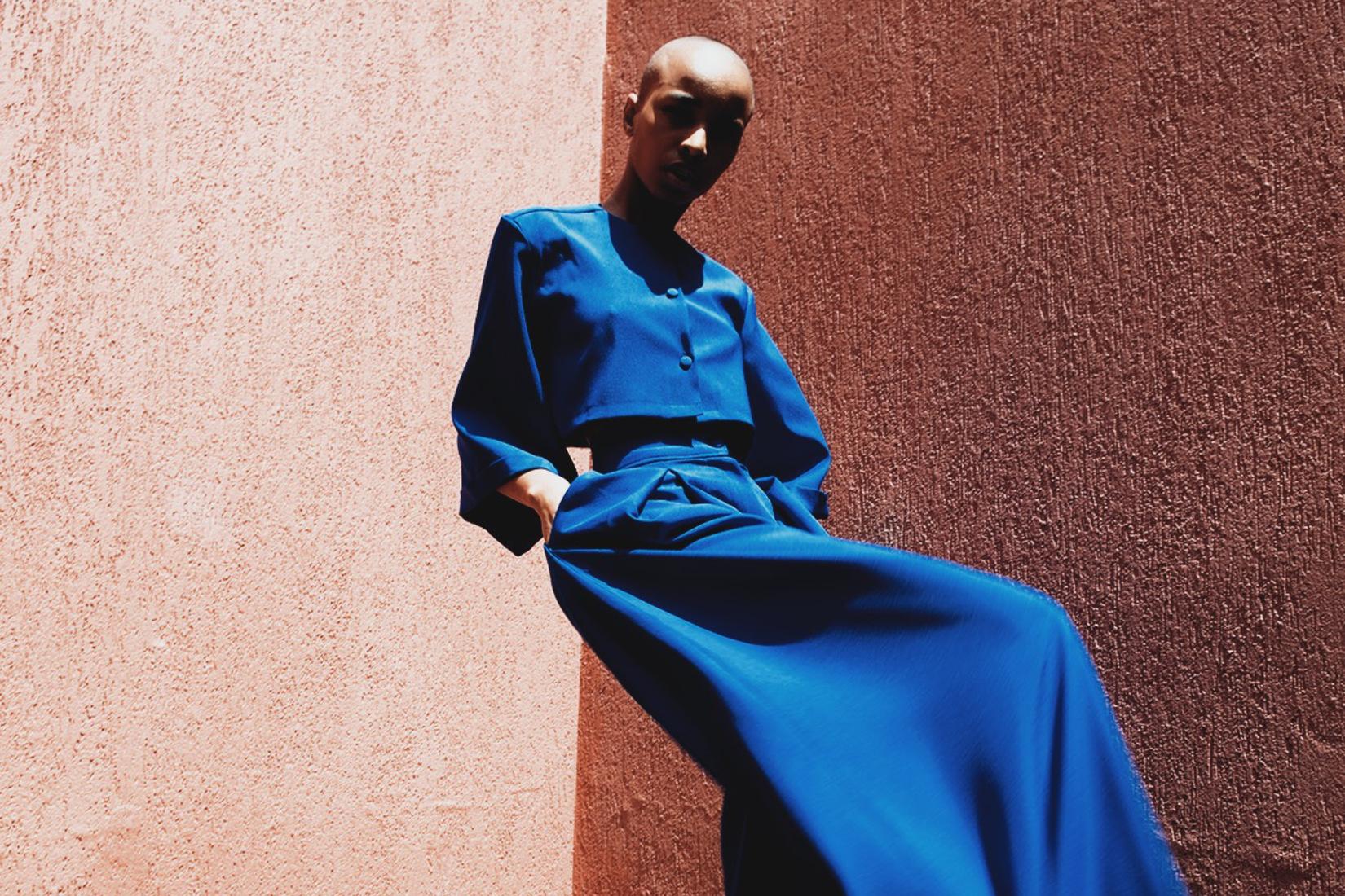 un mannequin porte un habit bleu derrière un mur rouge