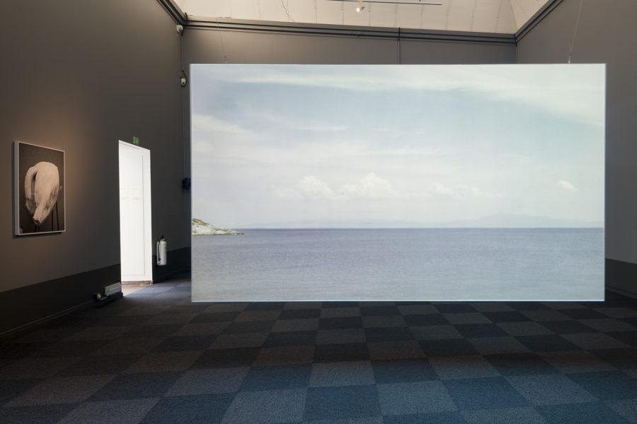 une pièce un peu sombre, une porte ouverte sur de la lumiére éclaire une grande toile au milieu de la pièce, représentant la mer et un horizon nuageux