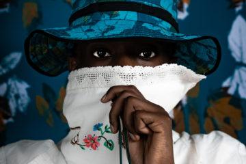 portrait : un jeune porte un bob bleu et e blouse böanche brodée qu'il remonte jusqu'à ses yeux q