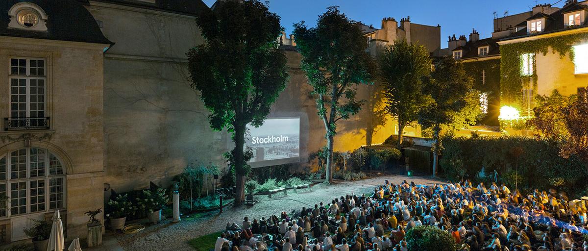 séance de ciné plein air dans le jardin , nuit tombée les spectateurs assisd ans l'herbe assistent à une projection dans el jardin de l'Hôtel de Marle
