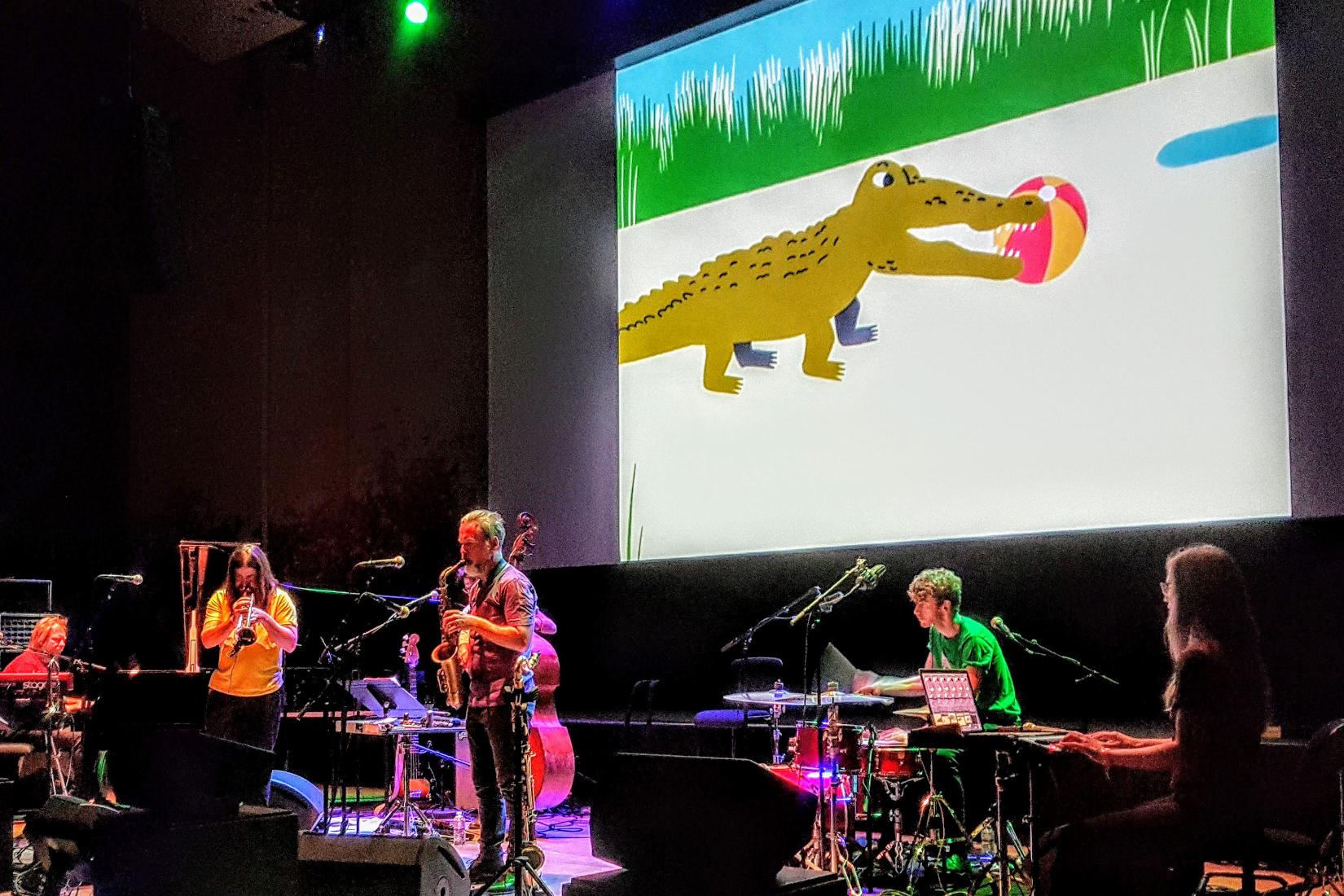 concert de jazzo par oddjob : écran derrière avec dessin animé et devant quintet joue du jazz