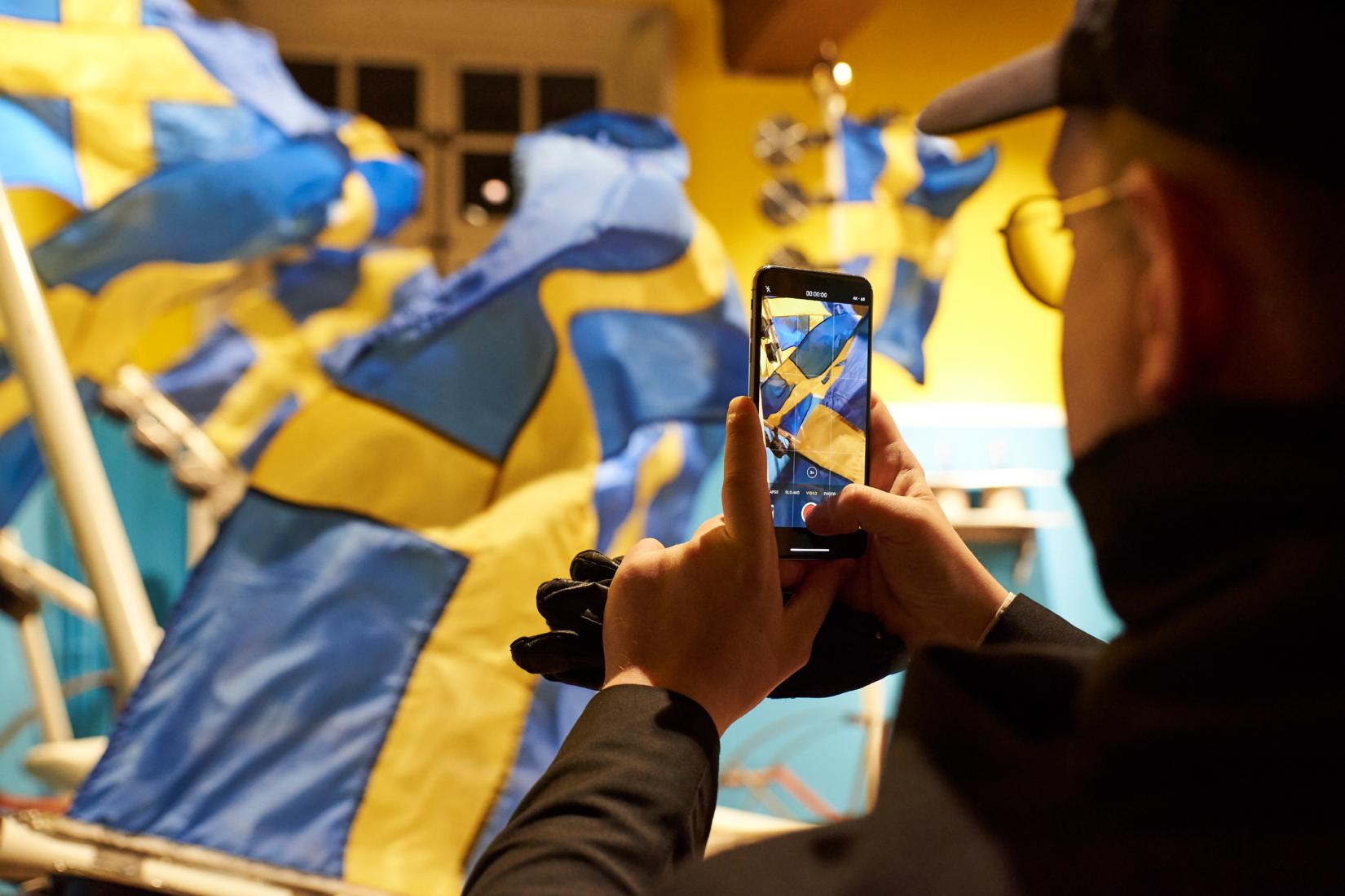 de dos un homme rpend en photo avec son smartphone des drapeaux suédois