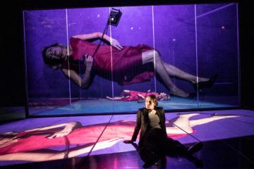 Une femme assise sur scène. Derrière un écran une autre femme en robe rouge allongée. Son image projeté sur l'écran et sur le sol .