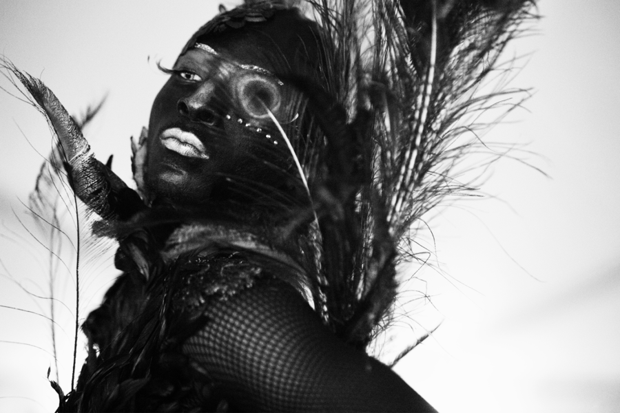 Black and white photo portrait of an artist dressed in feathers in voguing style.
