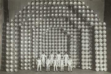 Image d'archive en noir et blanc des Ballet suédois, neuf danseurs se tiennent dans une formation devant un décor de scène