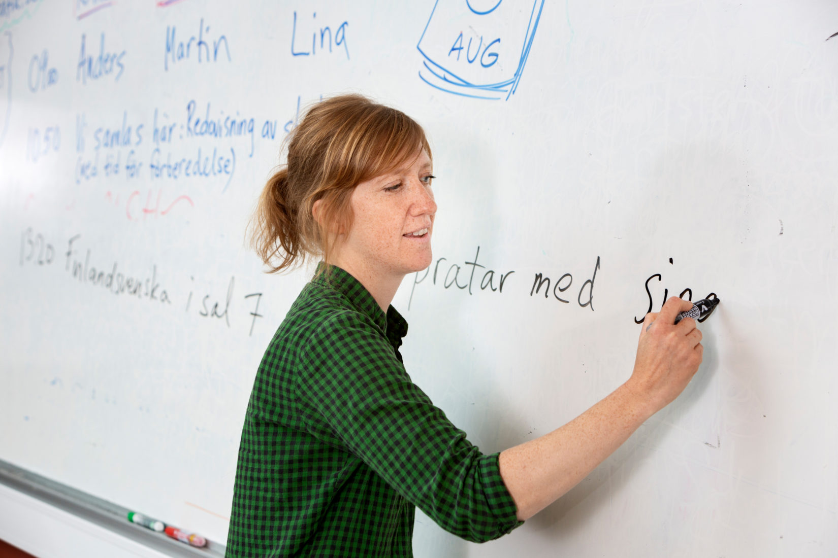 Woman writing on whiteboard.