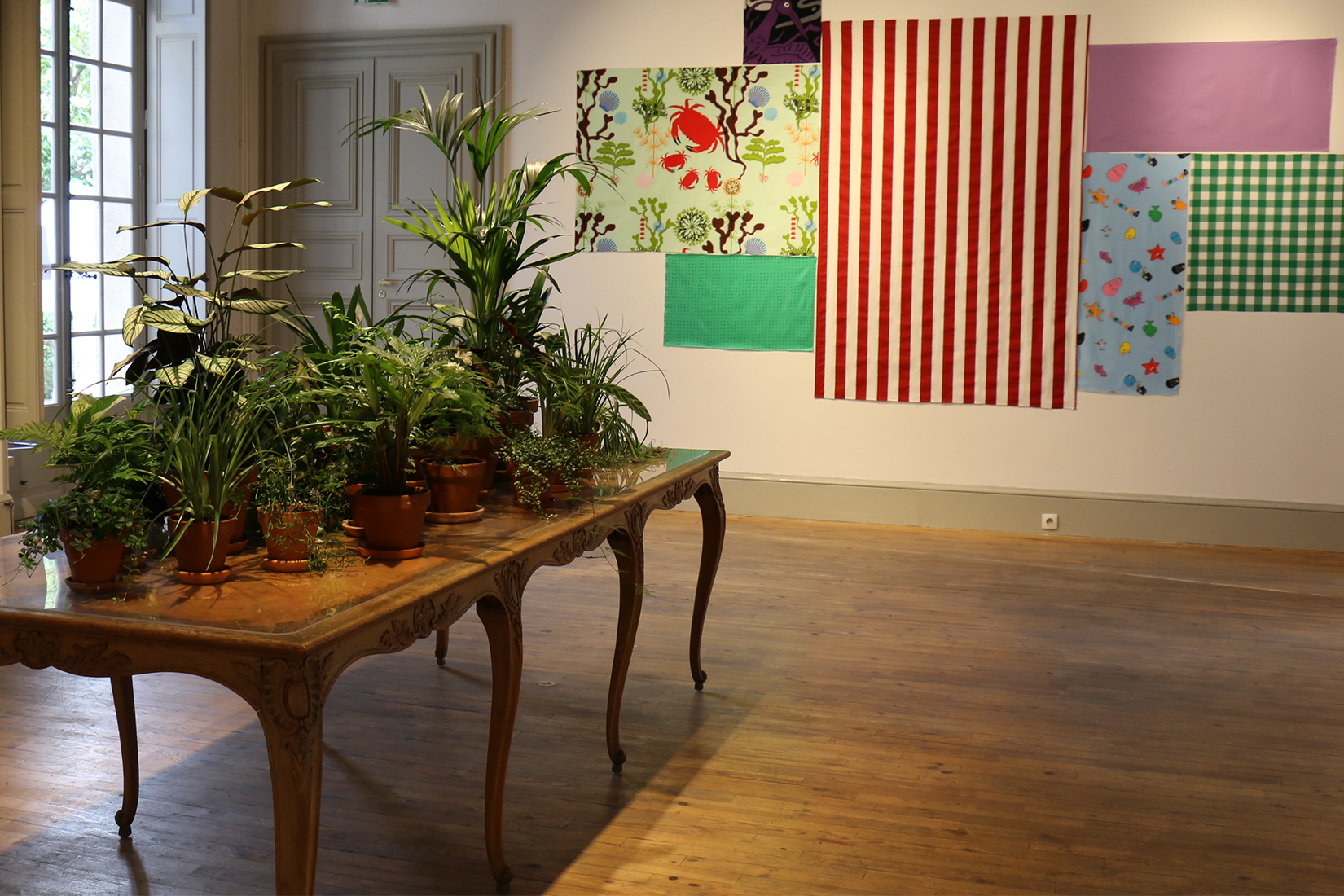 An antique table with an installation of plants on it, in front of a wall covered with different fabrics.