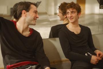 Deux danseurs se sourient, assis dos au miroir d'une salle de danse