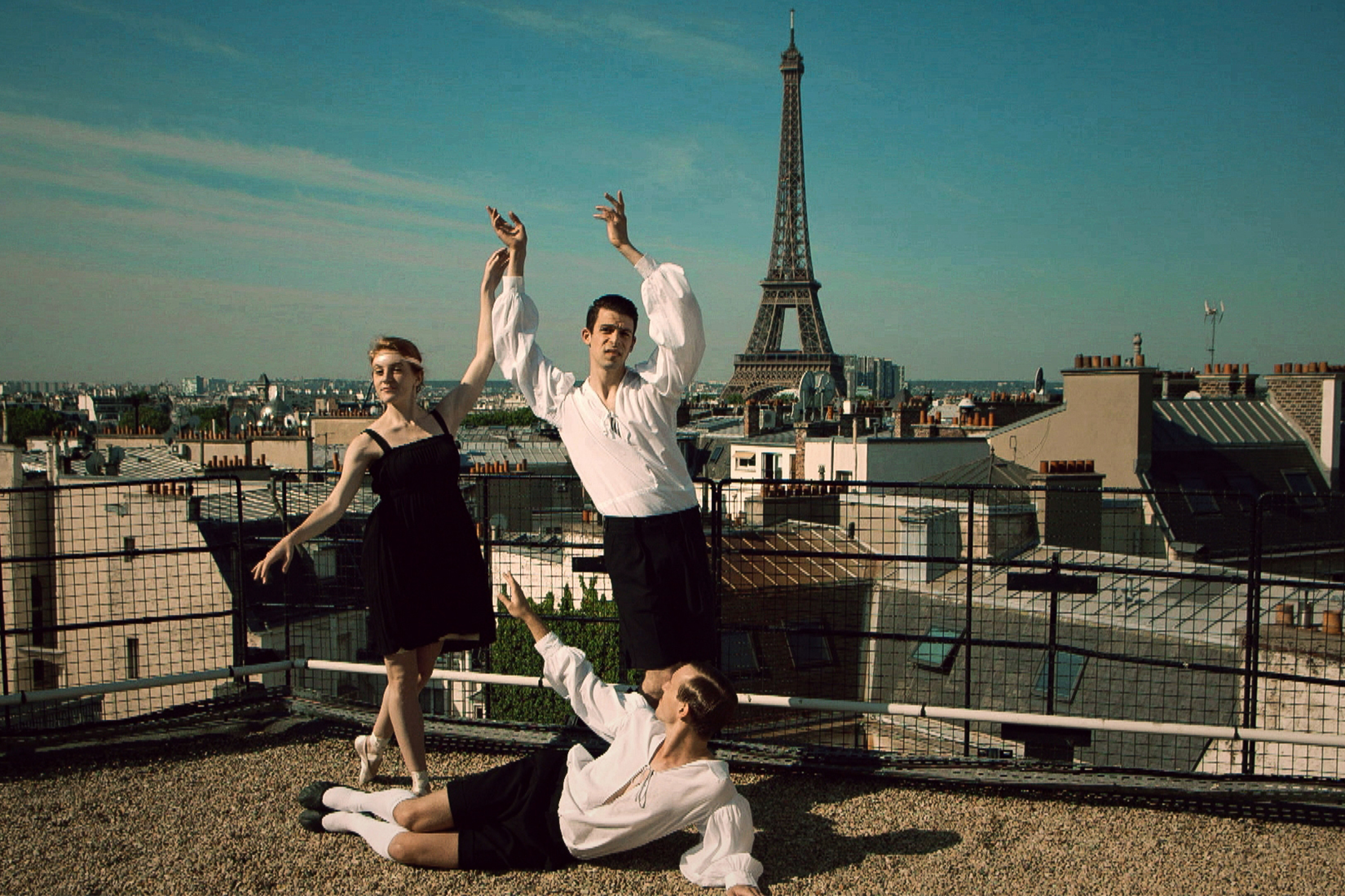 On the Parisian rooftops, dansers pose for the camera with the Eiffel Tower in the background.