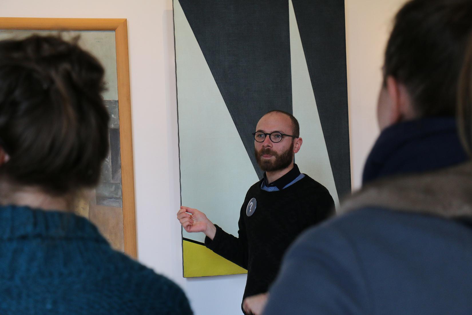 Image d'une visite guidée : un homme devant un tableau, au premier plan en flou des personnes de dos qui l'écoutent.