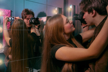A man and a girl about to kiss while filming themselves