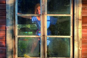 Une femme blonde debout derrière une vitre avec un pied sur le bord de la fenêtre