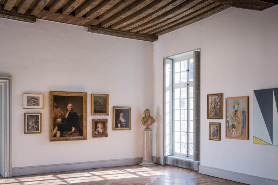 Une salle d'exposition avec plusieurs peintures et dessin