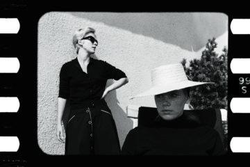 Two women in black looks in opposite direction