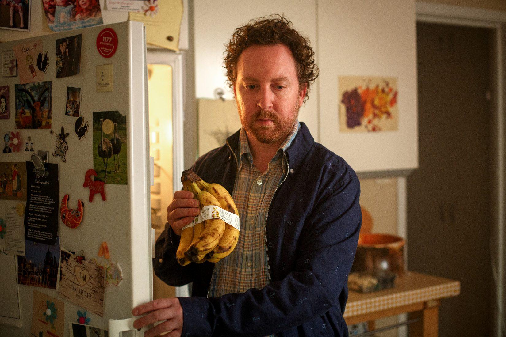 Un homme pensif tient des bananes dans sa main devant un frigo