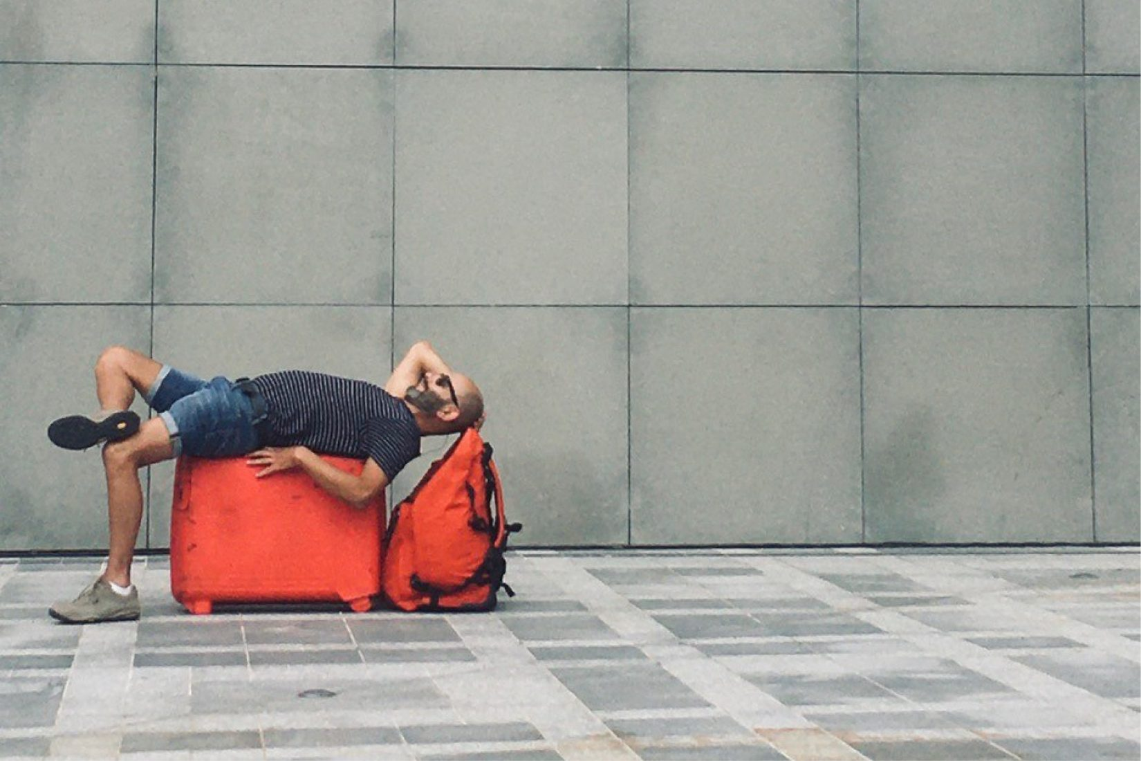 A man lying on a red travel bag