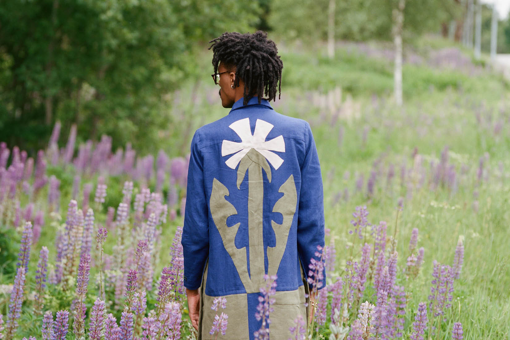 A man standing in a field of wild flowers, showing his back and wearing a long coat with a modern design of a flower.