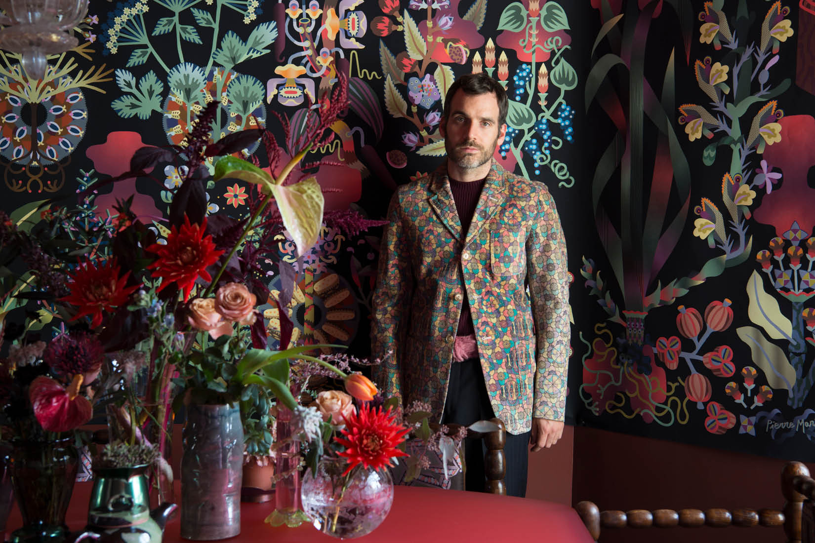 Pierre Marie is standing in front of his Ras El Hanout tapestry behind a table with flowers in vases.