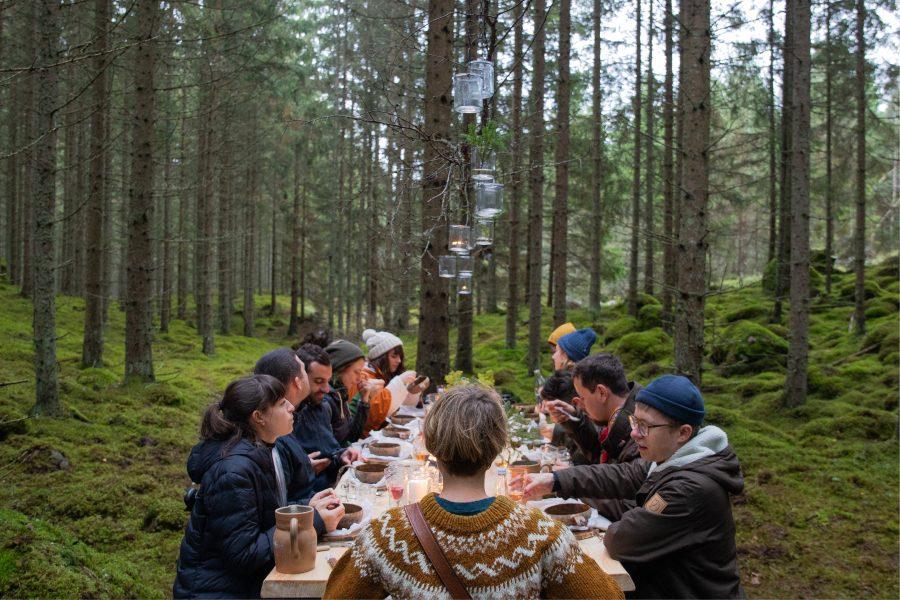 Des convives autour d'une table en pleine forêt