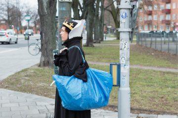 Liv Strömquist se tient debout, de profil, dans la rue, vêtue d'une longue robe noire et coiffée d'une couronne, avec un grand sac bleu Ikea à l'épaule.