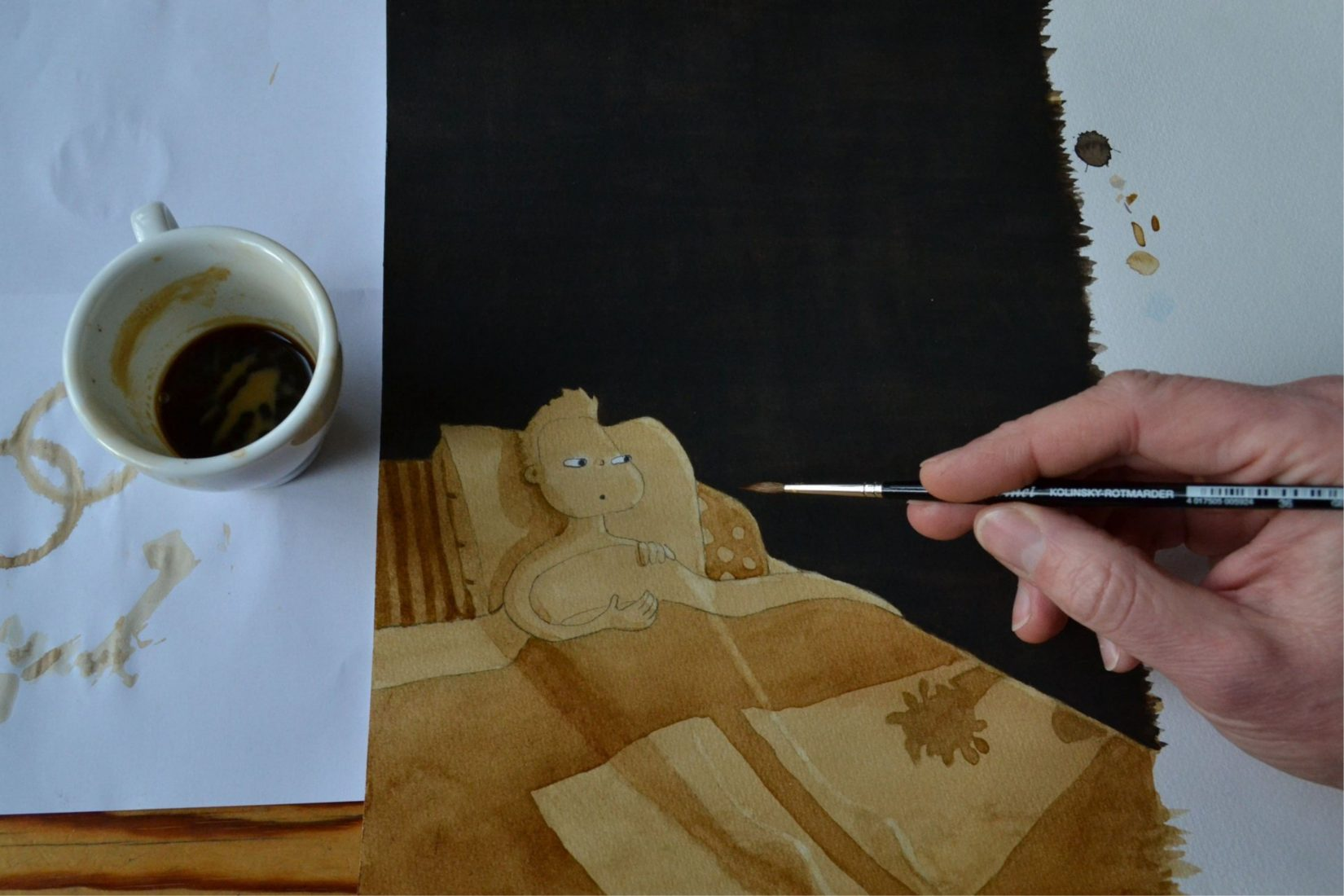 Painting with coffee of a little character in bed.