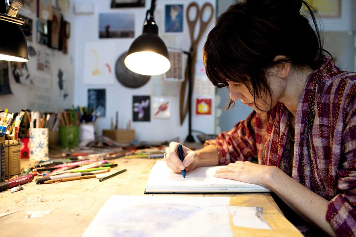 Beatrice Alemagna at her desk, drawing.